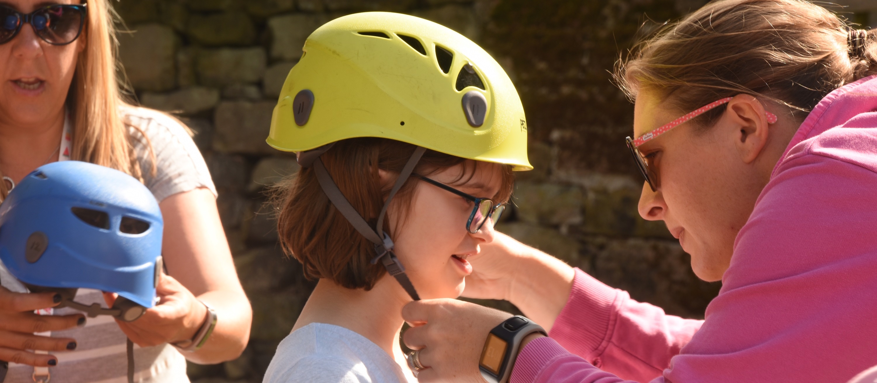 Image showing a lady helping a young girl put on a safety helmet
