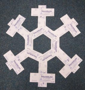 Books of white raffle tickets arranged on a dark background to make a snowflake shape