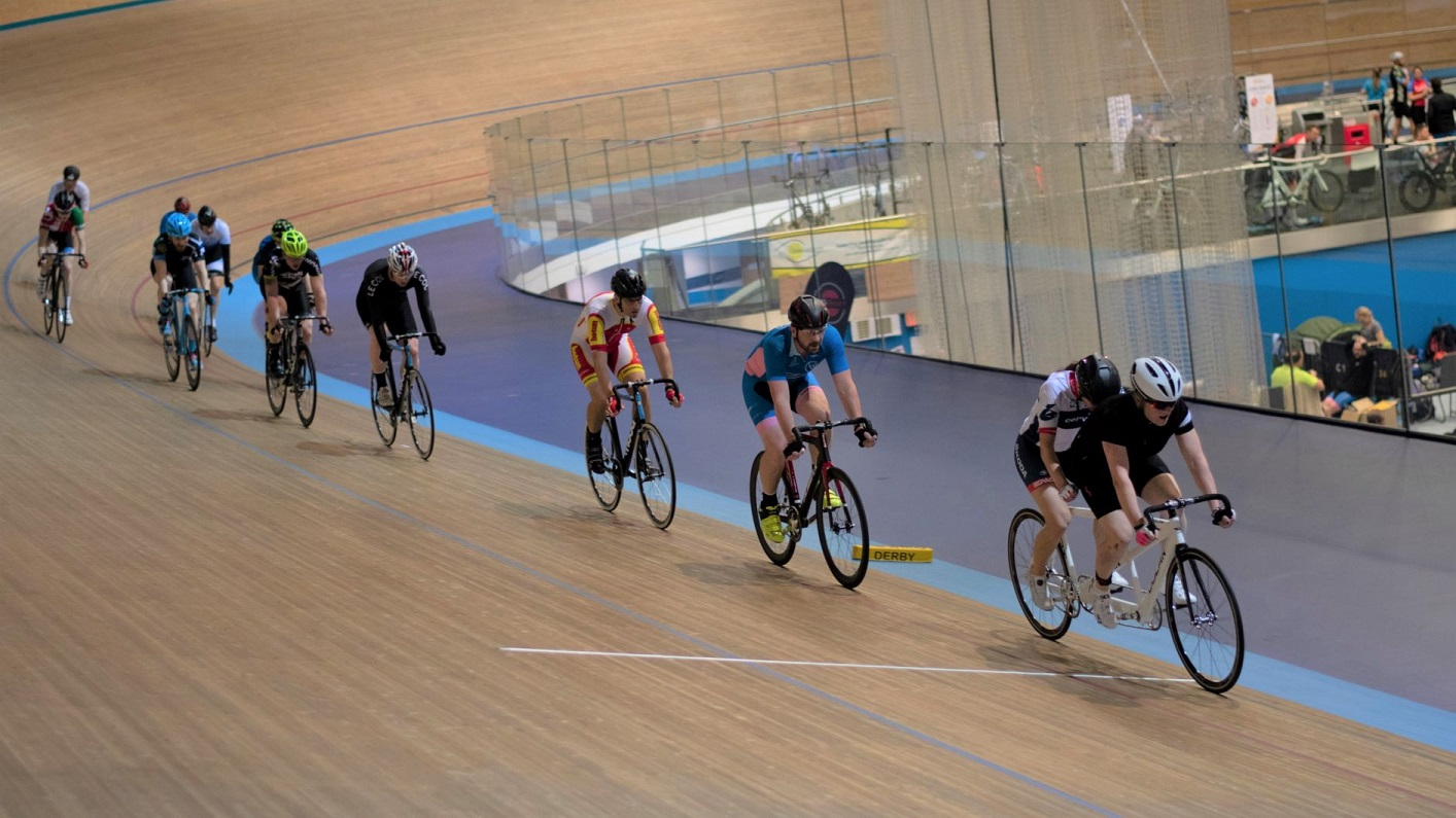 A tandem cycle leads the field on the track at Derby Velodrome