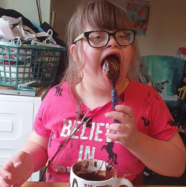 Visually impaired girl wearing glasses and a pink T shirt, licking chocolate cake mix off a spoon