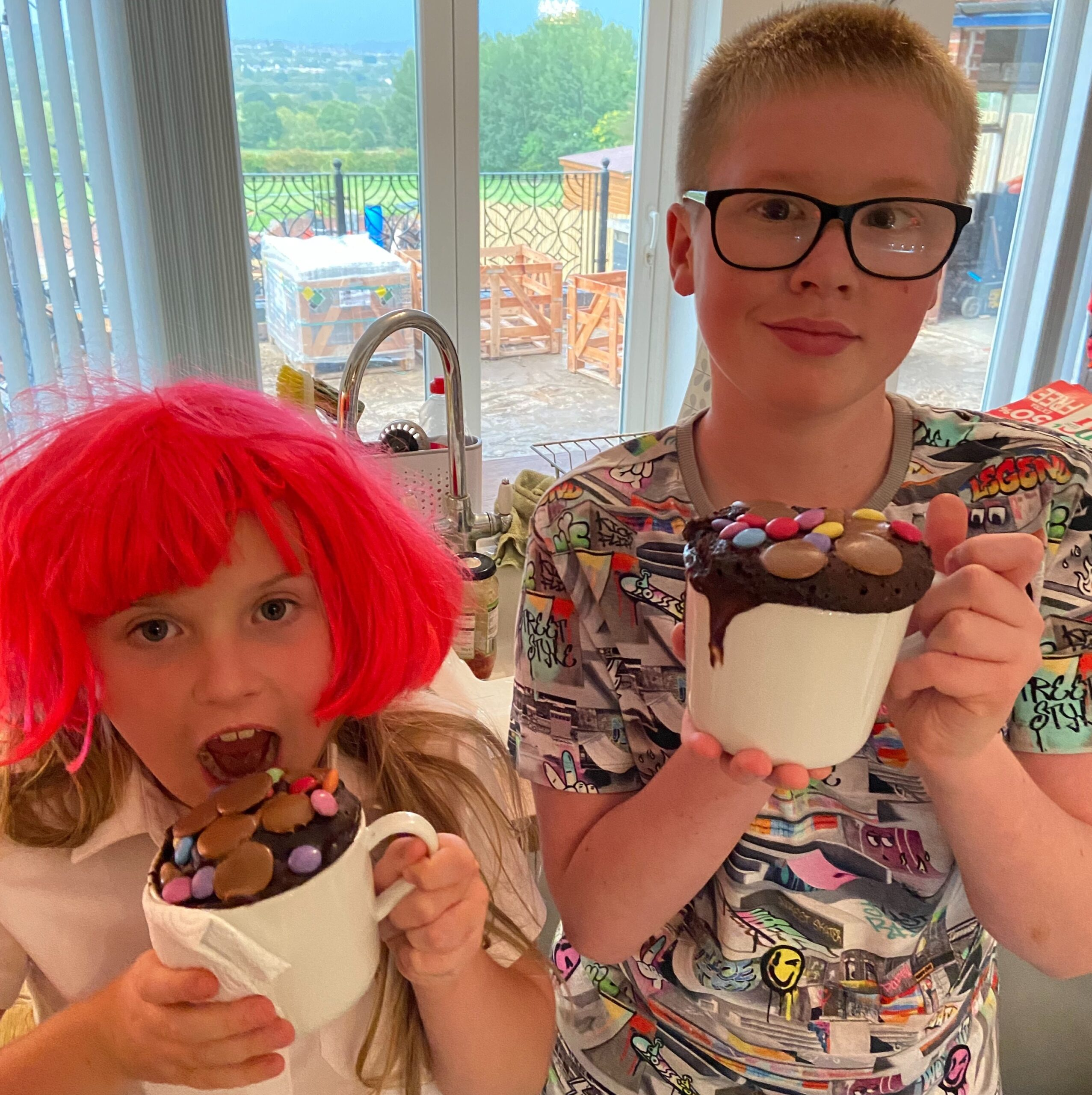 Girl wearing red wig and boy wearing glasses standing proudly with their mug cakes