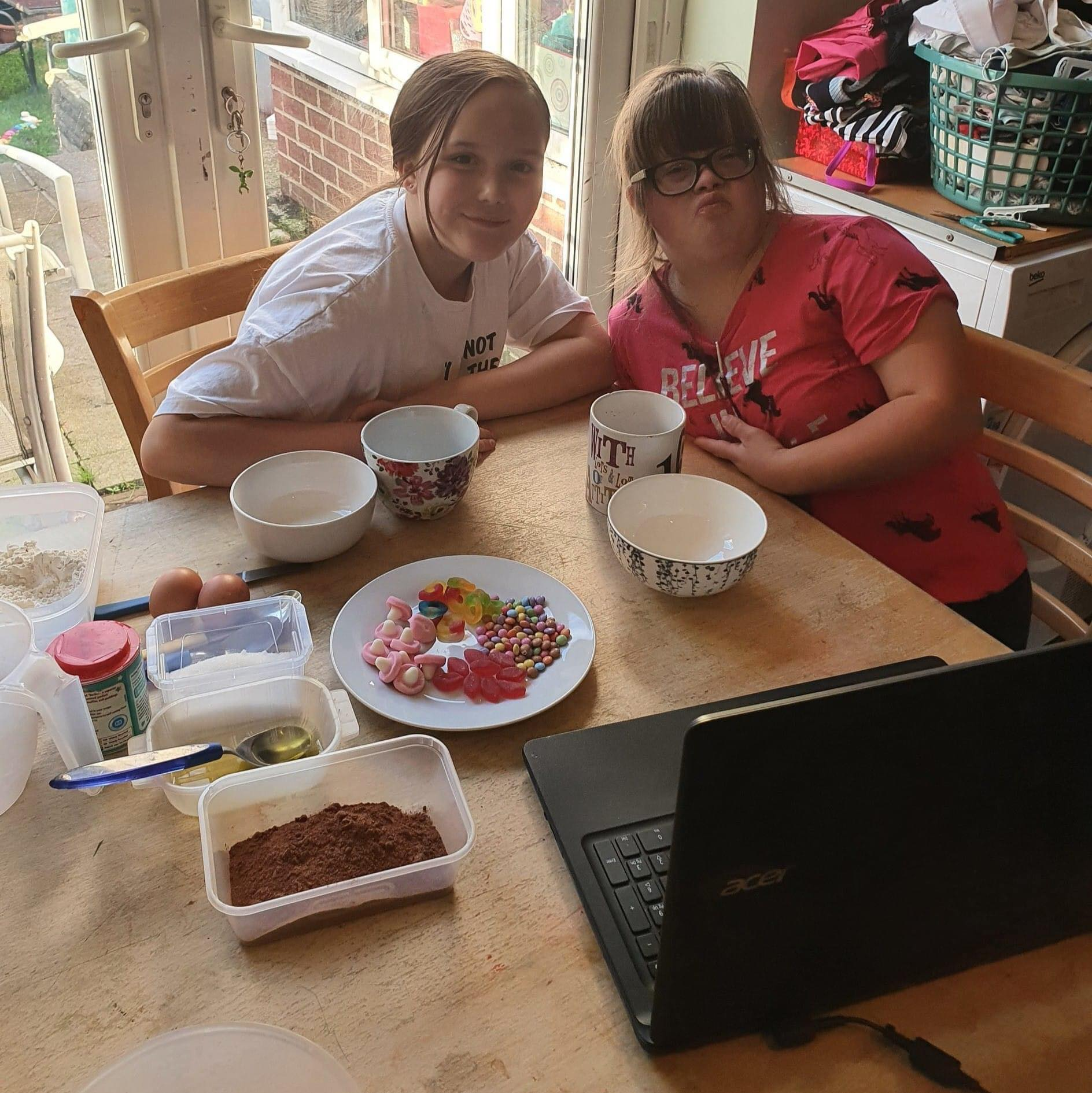 Two sisters watching a laptop for instructions on how to make their mug cakes