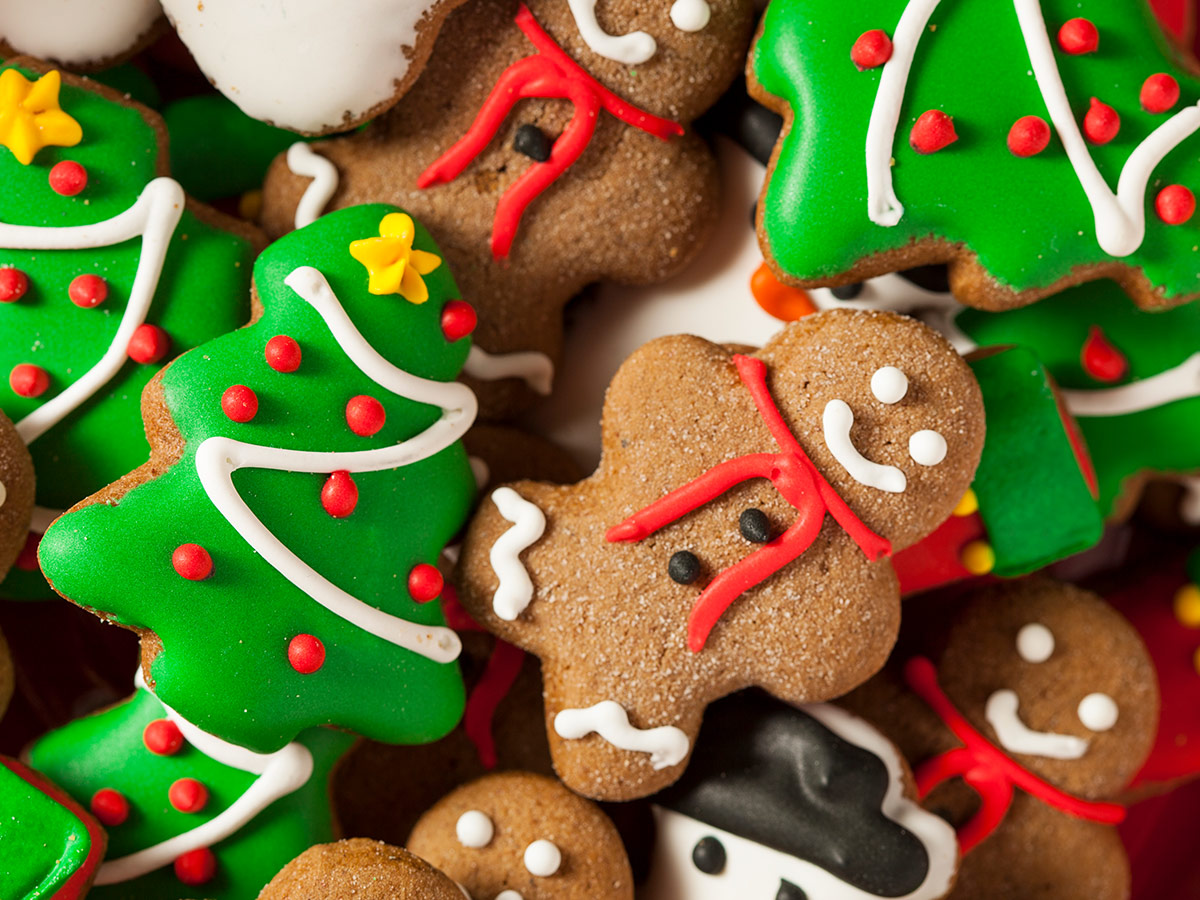 Biscuits, some with bright icing, and a smiling gingerbread man on the top of the pile