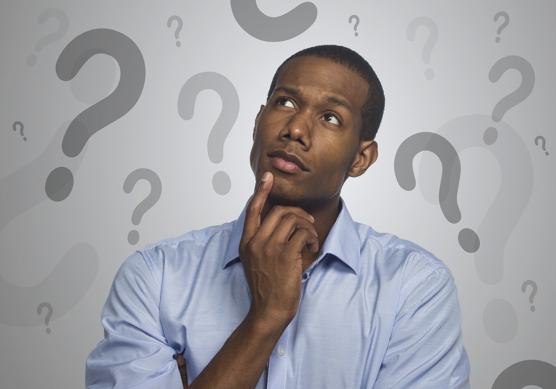 Man pointing at chin thinking, surrounded by question marks